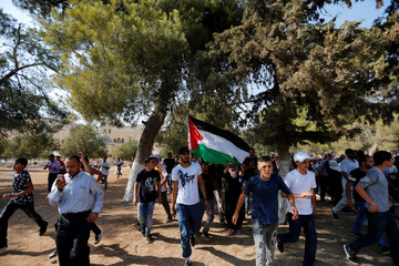 A Palestinian man carries a Palestinian flag upon entering the compound known to Muslims as Noble Sanctuary and to Jews as Temple Mount after Israel removed all security measures it had installed at the compound, in Jerusalem's Old City
