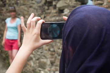 Girl is taking photo of woman on mobile phone