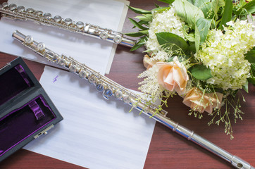 Two silver flutes  and a bouquet of flowers on the wooden table.