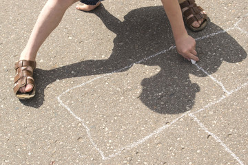 Children playing outside and drawing on the asphalt.