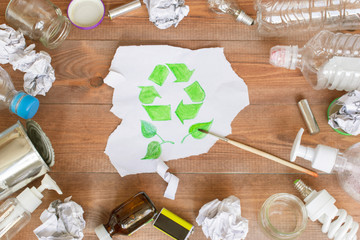 Ecology concept, a lot of recyclable objects and a drawn recycling symbol on the brown wooden background.