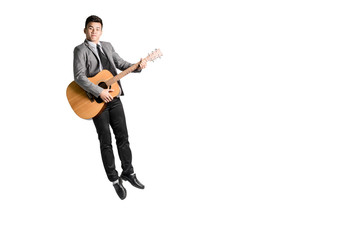 Portrait of a young business man jumping with guitar. Isolated on white background with copy space and clipping path
