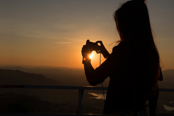 woman taking photos of sunset with mobile phone.