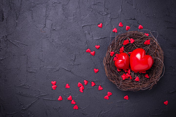 Hearts  in nest on black slate background. Flat lay.