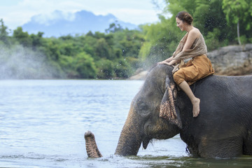 beuautiful girl in traditionalthai dress sitting on elephant showing lovely between human and animal,concept conserve nutuer