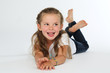 Kleines Mädchen liegt barfuß auf dem Boden und lacht