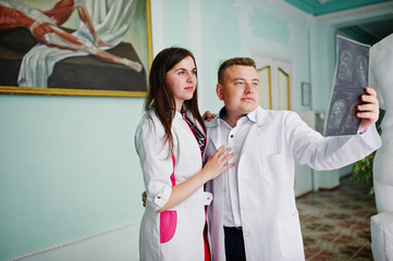 Skillful doctors are looking at x-ray image of their patient's body part in the hospital.