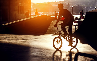Freestyle extreme street-biker boys under the bridge on artificial track with backlit sun effect and shadows