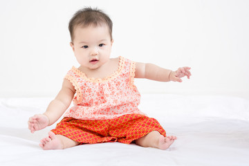 Portrait of a little adorable infant baby girl sitting on the bed and smile.