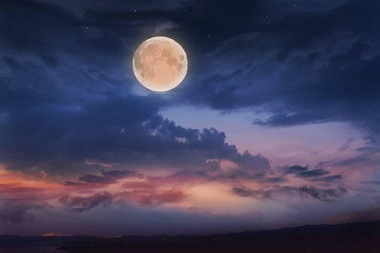 Glowing sunset and full moon  . Beautiful cloudy sky. Cloudy abstract background. Sunset colors.