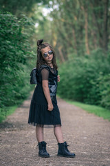 Fashionable girl is wearing black dress and sunglasses in garden