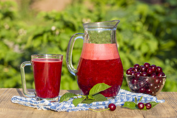 Dietary detox drink with red cherry in clear water with ice. Cherry juice in jug and in glass and ripe cherries in plate