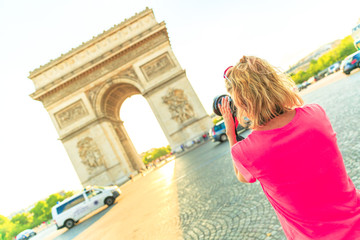 Travel woman photographer takes photos of Arch of triumph at Place Charles de Gaullethe from Champs Elysees. Female photographer in Paris, France, Europe. Arc de Triomphe on blurred background.