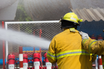 Firefighters spray water in fire extinguishers caused by explosive gas