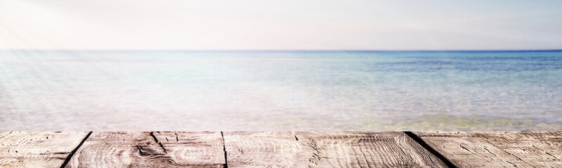 The Summer background - the wooden boards on the sea and sunlights ray