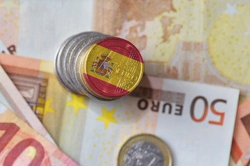 euro coin with national flag of spain on the euro money banknotes background