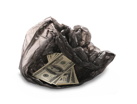 Crumpled, open black plastic garbage bag with hundred dollar bills inside it, isolated on white background