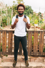 Portrait of beautiful afro man standing in front urban garden.