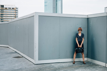 Fashionable Ginger Businesswoman in Front of Skyscrapers
