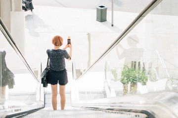 Ginger Woman Taking Picture with a Mobile Phone in The City