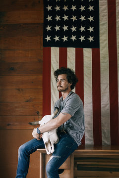Portrait of a Confident Man Sitting in Front of an American Flag Holding a Bull Skull