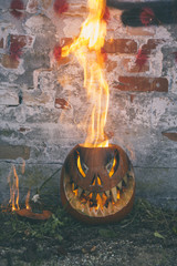 Halloween carved pumpkin burning outdoors
