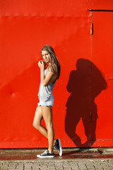 girl standing in front of red wall