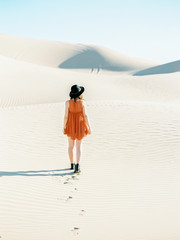 Young woman walking on sand dunes