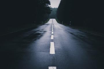 Regen nasse dunkle Straße durch den Wald