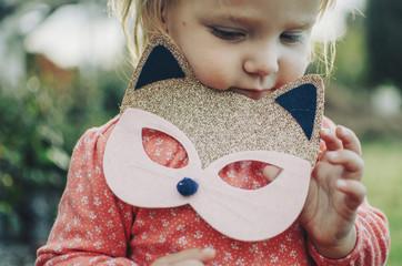 Little girl holding glitter cat mask