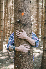 Young man hugging a tree