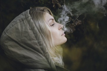 Young blonde woman with a hood on blowing smoke out her mouth