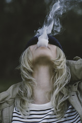 Blonde girl with a hat blowing smoke out her mouth.