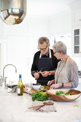 Mature couple with grey hair cooking in kitchen of luxury home