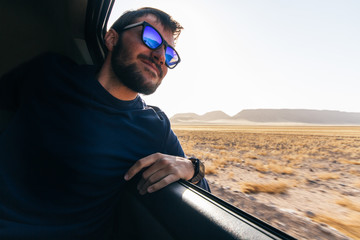 Young man leaning on the window of a car enjoying the view while traveling at sunset on adventure travel