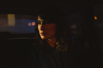 Portrait of beautiful woman at back seat of a car