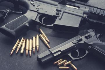 Handgun with rifle and ammunition on dark background