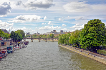 Seine River in Paris with its boats, architecture and people on the banks