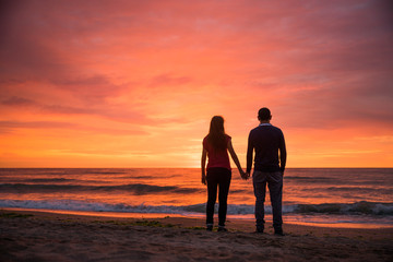 Romantic couple holding hands caring for each other at sunset. Valentines theme. Dramatic sunset. Colorful sky. Sea side romance silhouettes concept