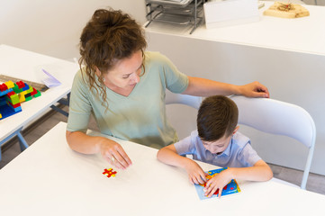 teacher woman and preschooler boy playing with puzzle game in the classroom