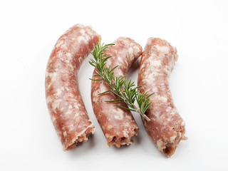 From above uncooked sausage with rosemary on white background. Isolated.