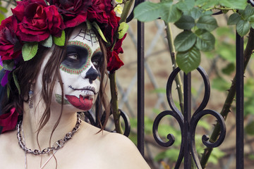 Beautiful woman in makeup traditional Mexican Calavera sugar skull on the background of an iron fence with spikes. Day of the dead. Halloween celebration.