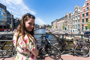 View of a tourist girl at the Rokin promenade and canal
