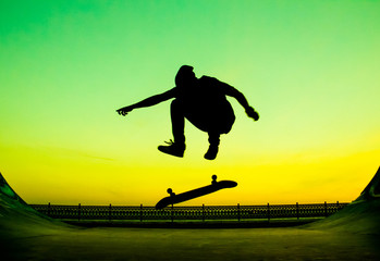 Young skateboarder does the trick on a bright green background