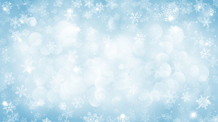 Christmas background of snowflakes with bokeh effect in light blue colors