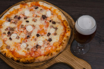 Hot piece of pizza with melted cheese on a rustic wooden table and beer