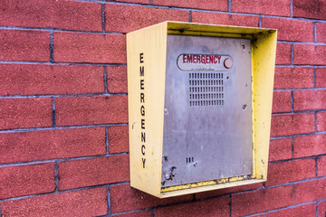 Emergency single button call station on brick wall closeup