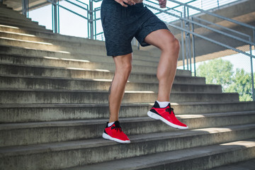 Close up of a man's legs running down the steps