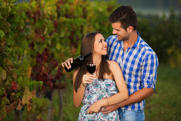 Couple standing in the beautiful vineyard and looking each other