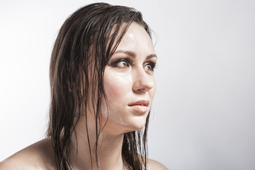 Beauty Concepts and Ideas. Portrait of Caucasian Sensual Brunette Girl Showing Wet and Shining Skin and Wet Hair. Creative Makeup. against Grey.